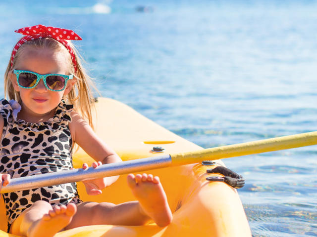Little cute girl kayaking in the clear blue sea